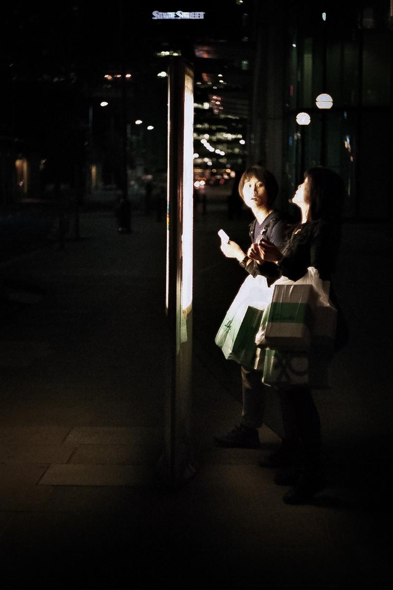 Analoge Fotografie: Damen warten an der Haltestelle