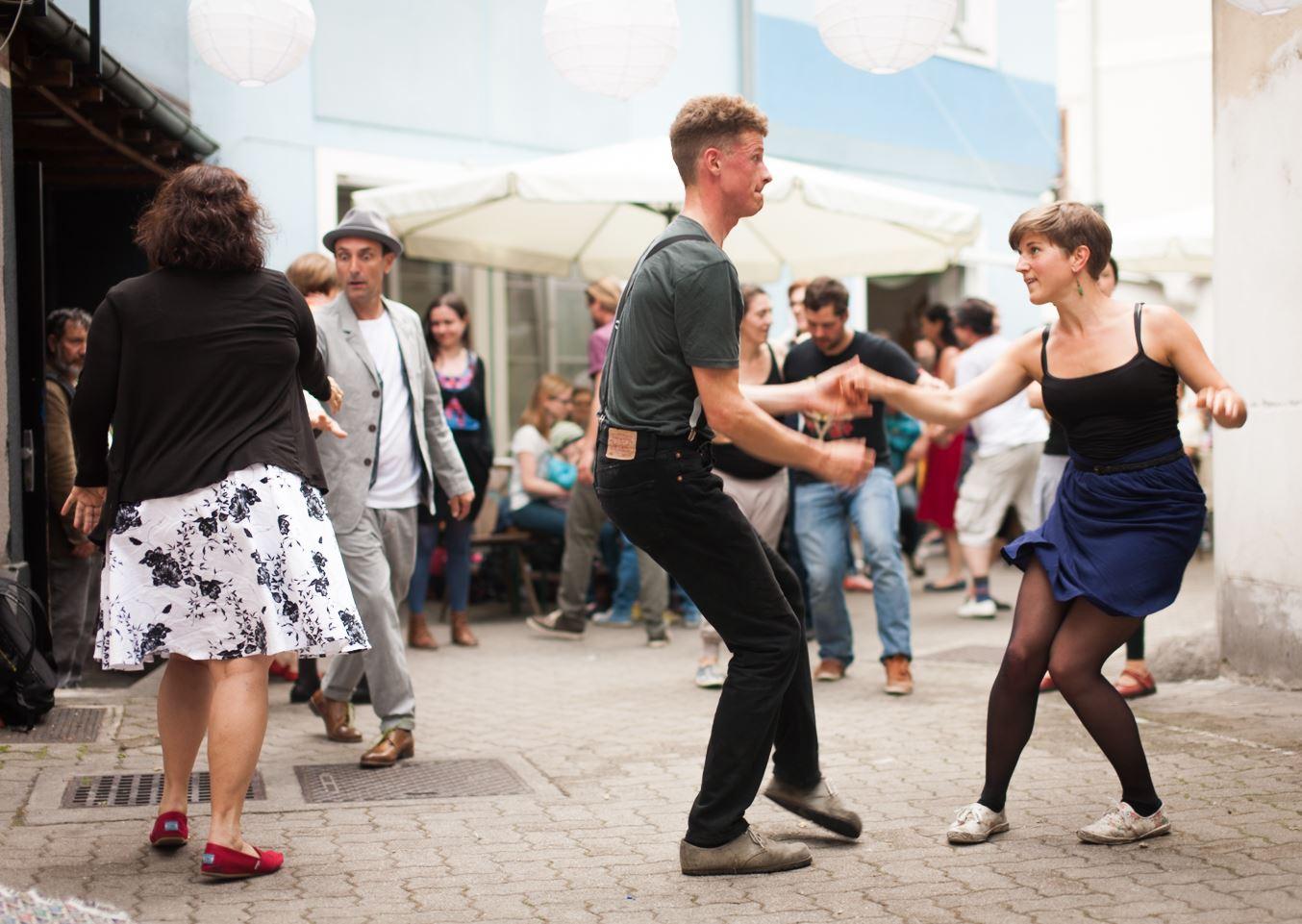 Tanzende Menschen auf der Straße © Darius Kromoser
