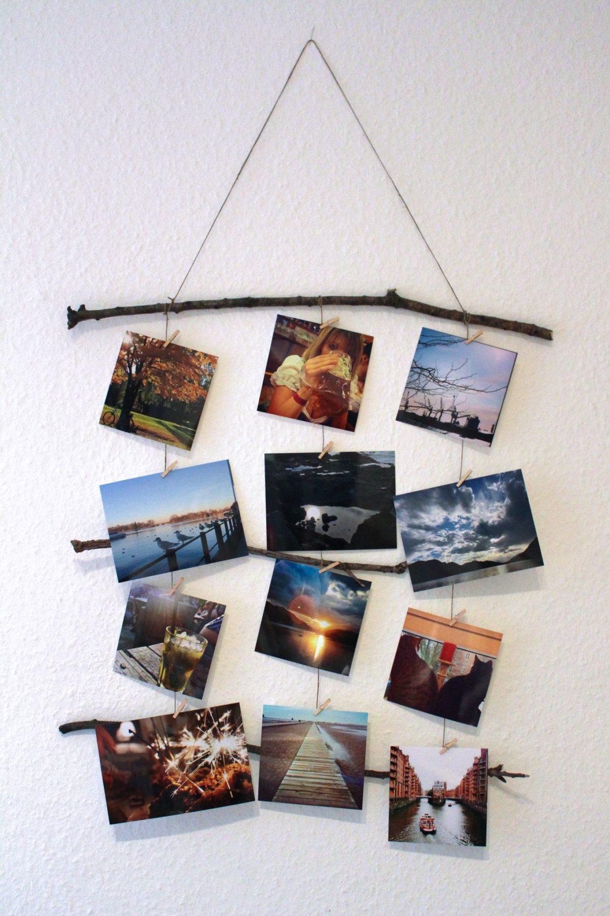 Wanddekoration aus Ästen und Fotos