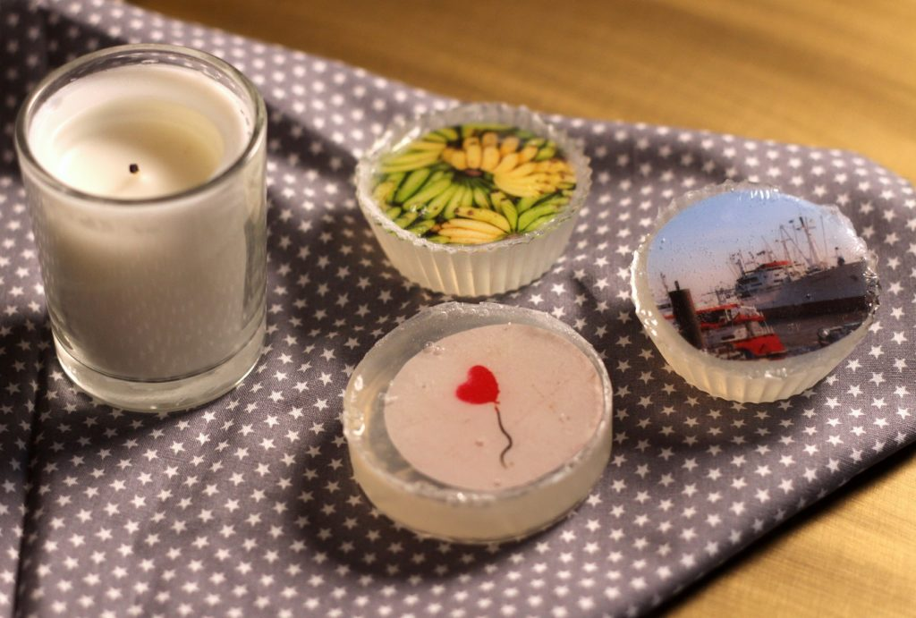 Drei Foto-Seifen auf Tischdecke mit Kerze