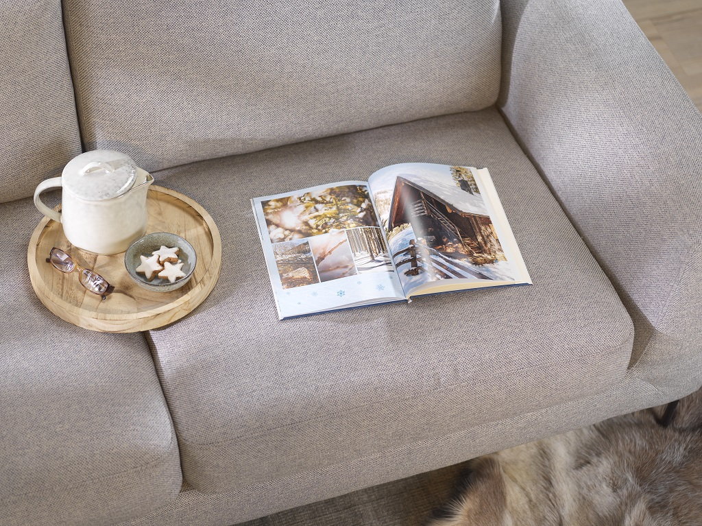 Ein CEWE Fotobuch aufgeschlagen auf der Couch mit Weihnachtsgebäck auf Tablett